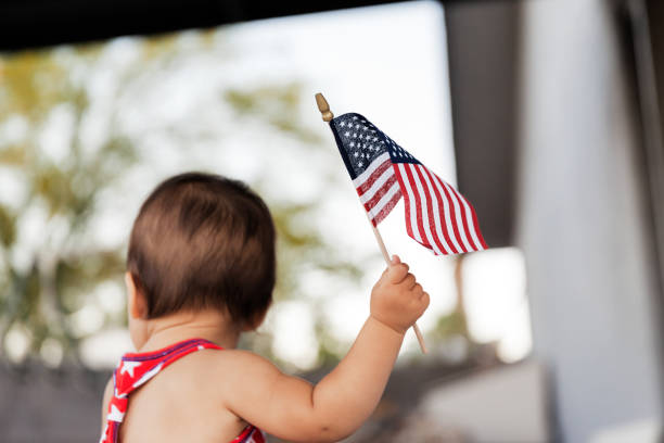 Baby girl celebrating  4th of July with USA flag in hand, Traditional American Holiday stock photo
