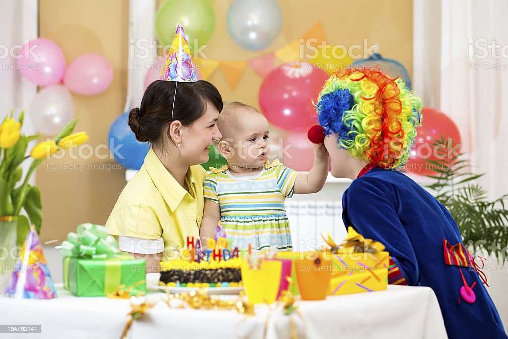 baby girl celebrating first birthday with parents and clown royalty-free stock photo