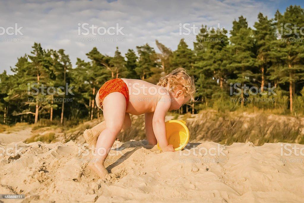 Baby girl climbimg on sand dune against pine forest background stok fotoğrafı