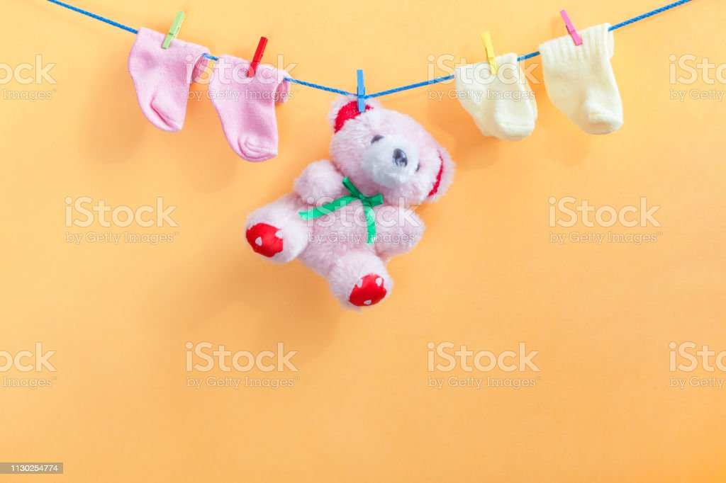 Baby girl clothes and toy bear. Newborn goods hanging on clothesline