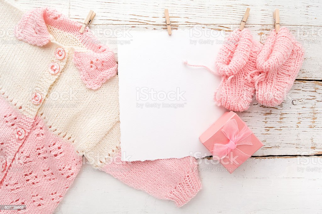 Baby girl clothes with blank card on white wooden background stock photo