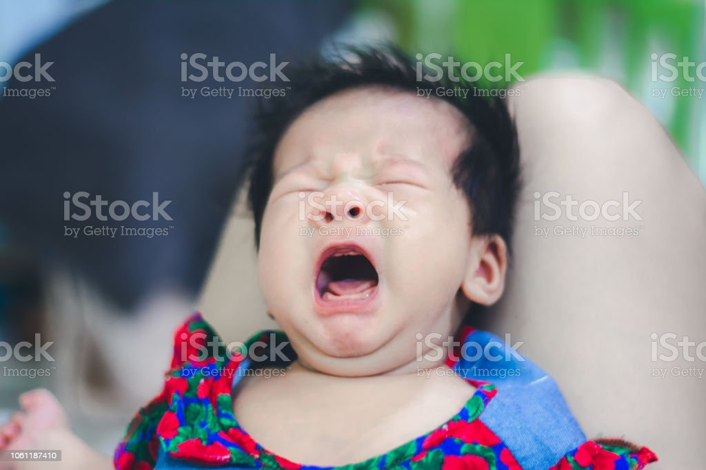 baby girl crying hungry for mother on Aunty's knee stock photo
