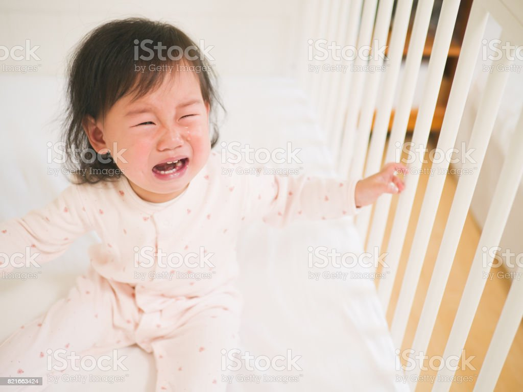 Baby girl crying in cot bed royalty free stock photo