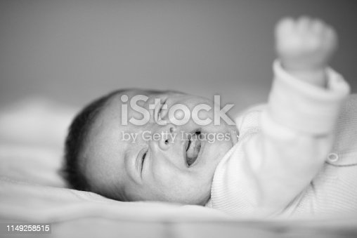 black and white portrait of baby girl crying, lying on bed.