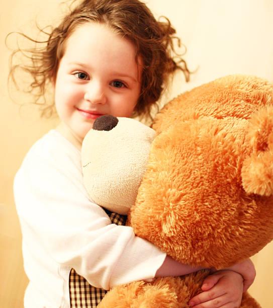 baby mädchen kuscheln mit teddybär - lila teenschlafzimmer stock-fotos und bilder