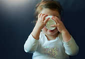 Baby girl holding cup of tea drinking, feeling relaxed indoors on the couch, covering face