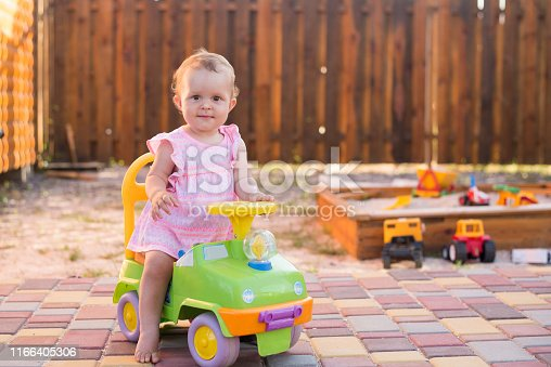 Baby girl driving a toy car at the playground outdoor, summer background, copy space