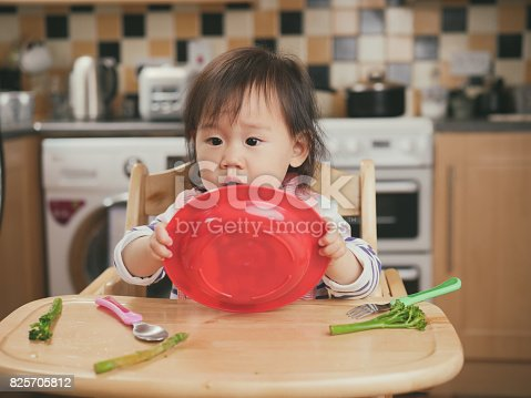 istock baby girl eating at home 825705812