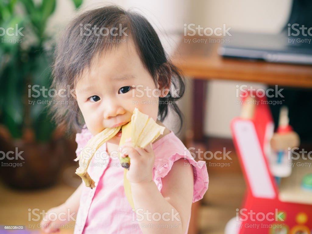 Niña bebé comer banana foto de stock libre de derechos