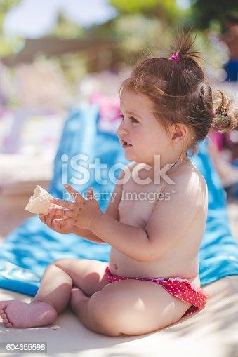 istock baby girl eating coan on a beach 604355596