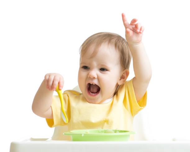 Baby girl eating her dinner isolated on white – Foto