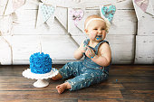 A baby girl scrunches up her nose and smiles as she tastes her first birthday cake.