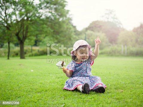 istock baby girl eating icecream in summer garden 838952056
