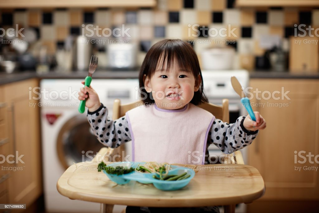 Baby girl eating messy at home kitchen