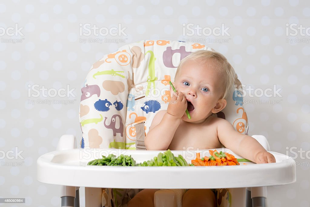 Baby girl eating raw food stock photo