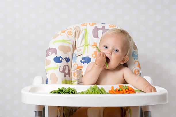 Bebê Menina comendo alimentos crus - foto de acervo