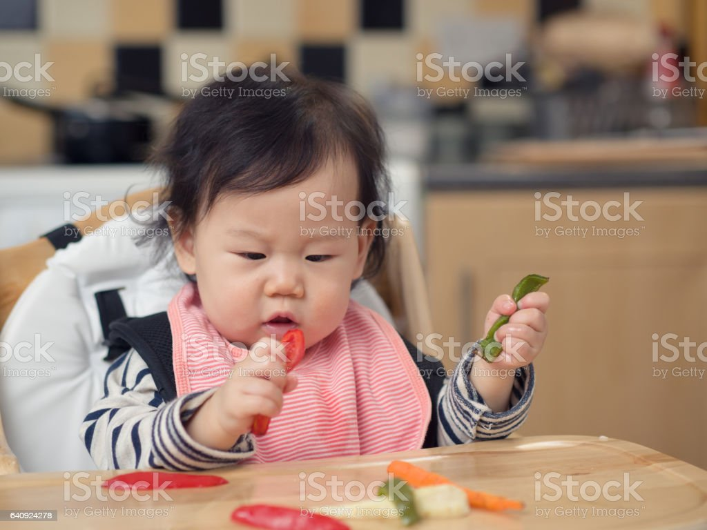baby girl eating roasted vegetable first time stock photo