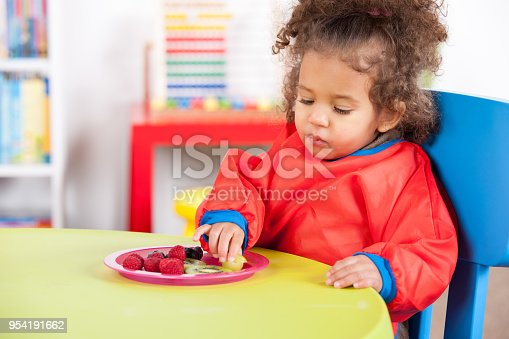 Baby girl eating various fruits in plate. Toddler is sitting at table in classroom. She is having curly hair.