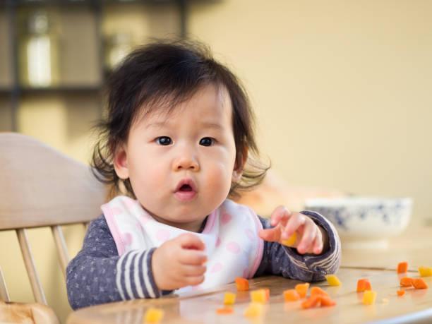 petite fille mangeant légumes première fois - état solide photos et images de collection