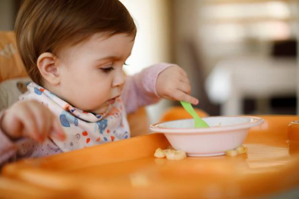baby girl enjoying her delicious lunch - allergie alimentari foto e immagini stock