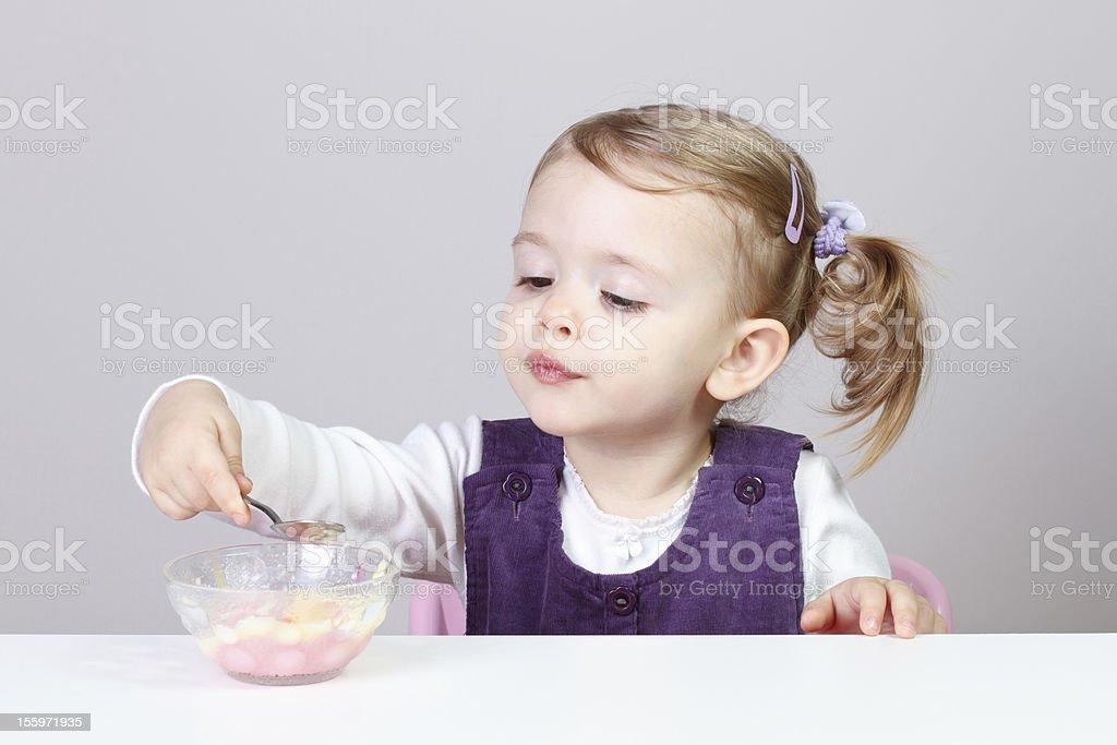 Baby girl having fun while eating royalty-free stock photo