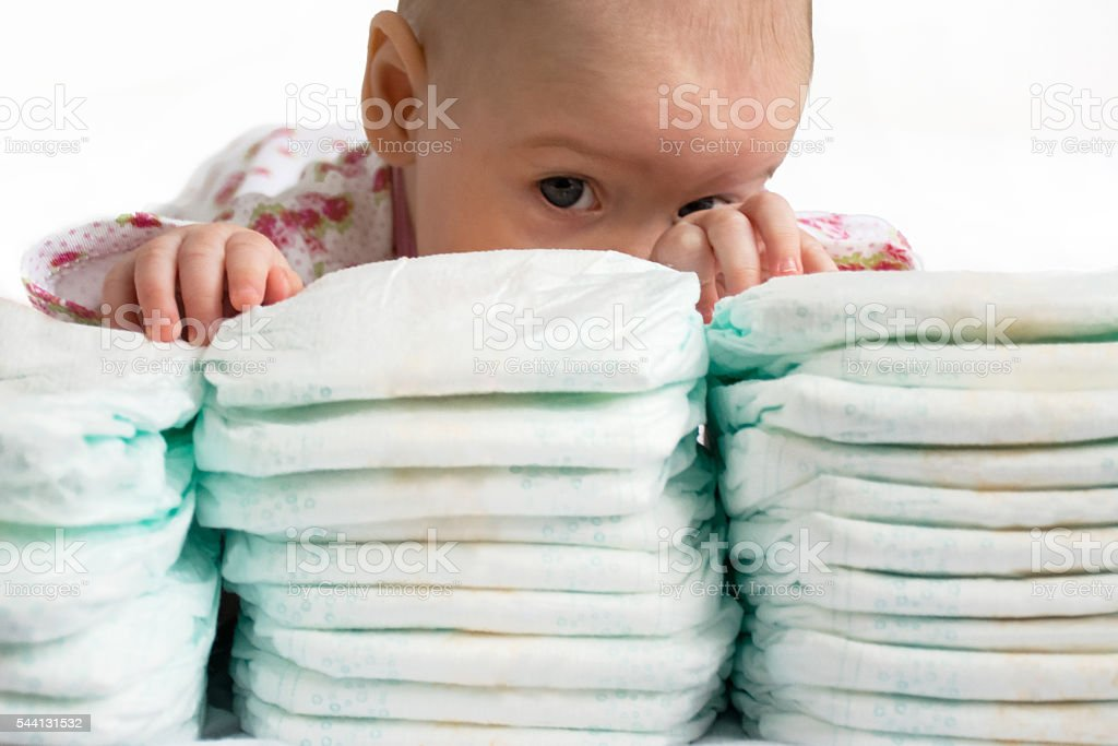 baby girl hidden behind stack of diapers stock photo