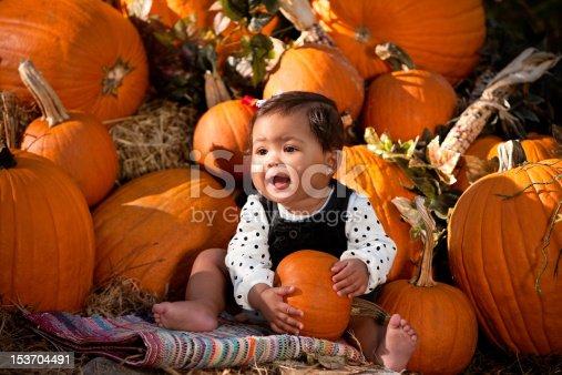 istock Baby girl holding a pumpkin 153704491