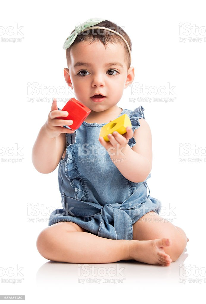 Baby girl holding and looking at toy blocks - foto de stock