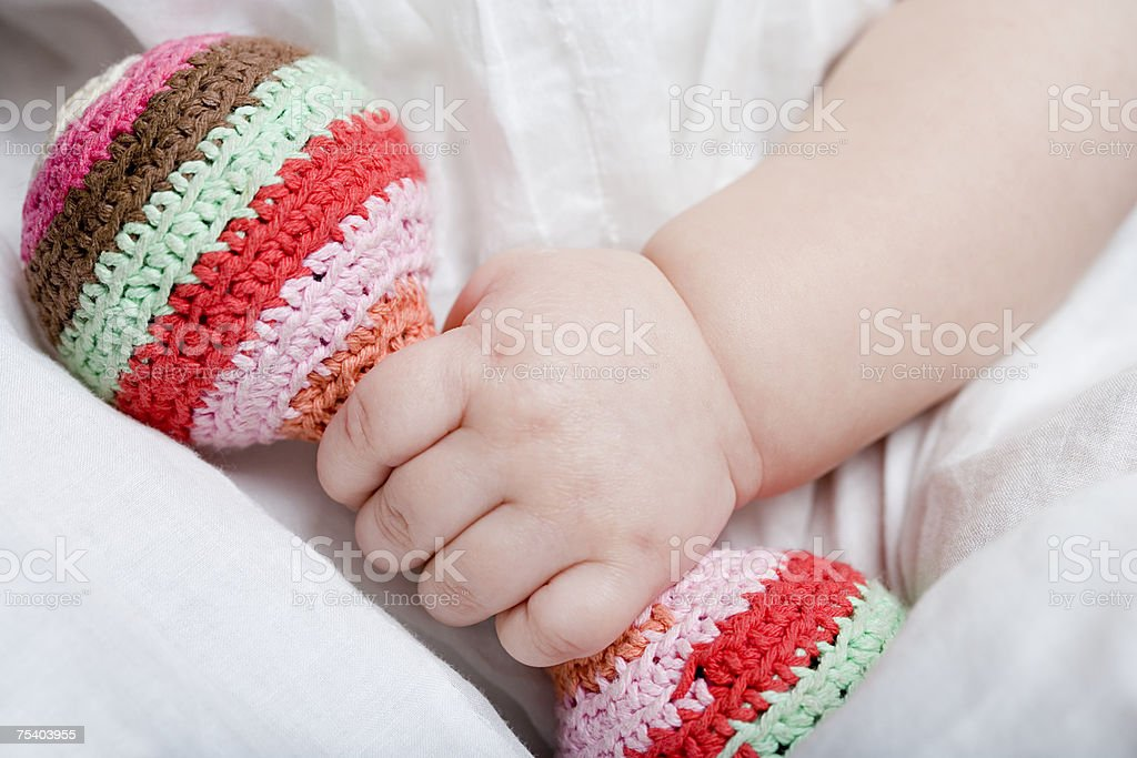 Baby girl holding rattle stock photo