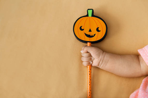 Baby girl holding stick with pumpkin on orange backgroud stock photo
