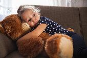 Baby girl hugging her teddy bear