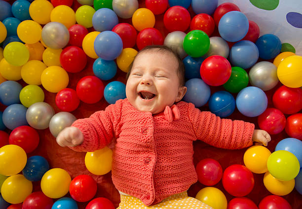 baby girl in a ball pit baby girl laughing in a sensory ball pit sensory perception stock pictures, royalty-free photos & images