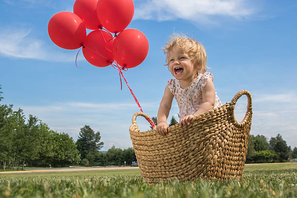 Baby Girl in a Basket with Red Balloons stock photo