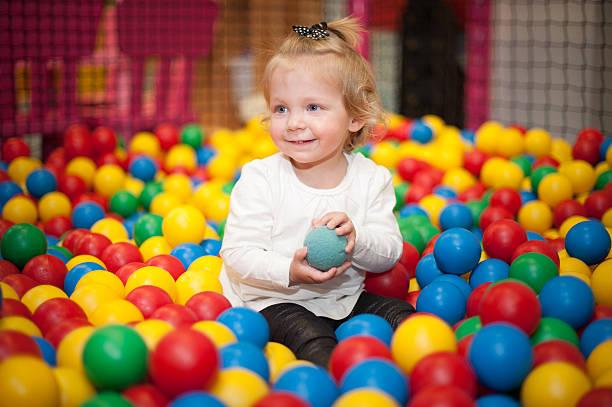 Baby girl in ball pool stock photo