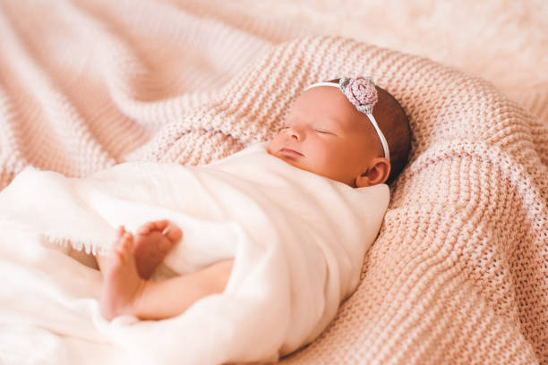 Baby girl in bed Cute smiling baby girl sleeping in cot closeup. Childhood. baby blanket stock pictures, royalty-free photos & images