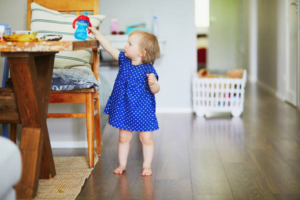 Baby girl in blue dress putting her water bottle on the table stock photo