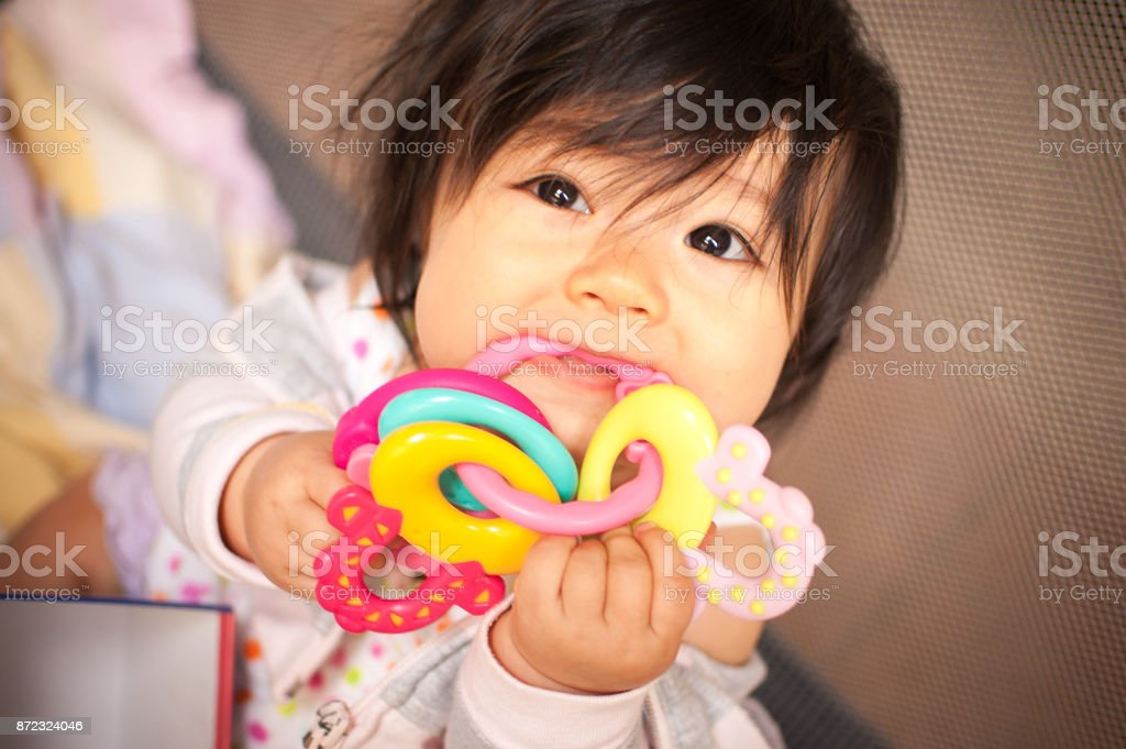 Baby girl in discomfort chewing on teething rings stock photo