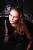 istock Baby girl in Halloween costumes on black background. 1174126821