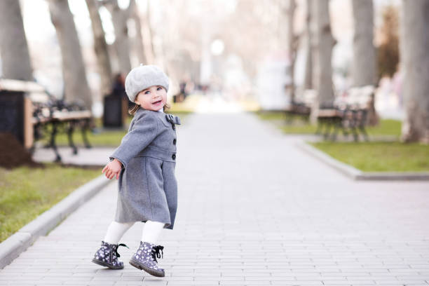 Baby girl in park Smiling baby girl 1-2 year old wearing stylish french style jacket running in park outdoors. Looking at camera. Childhood. beret stock pictures, royalty-free photos & images