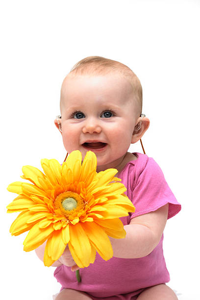 A baby girl in pink holding a flower stock photo