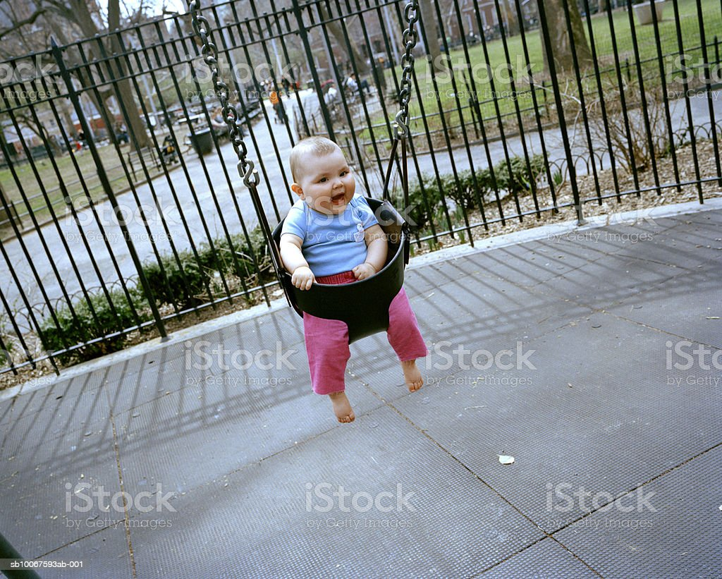 Baby girl (15-18 months) in playground swing royalty-free stock photo