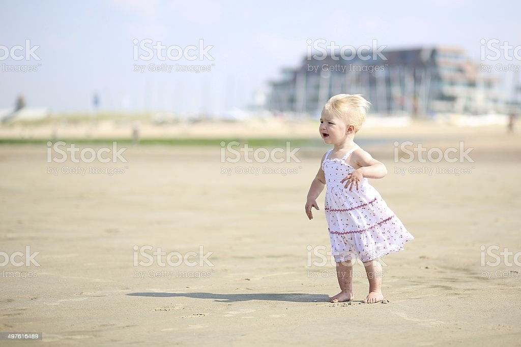 Baby girl in pretty dress walking along the beach royalty-free stock photo