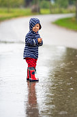 baby girl in rain clothes standing in puddle on rural village road