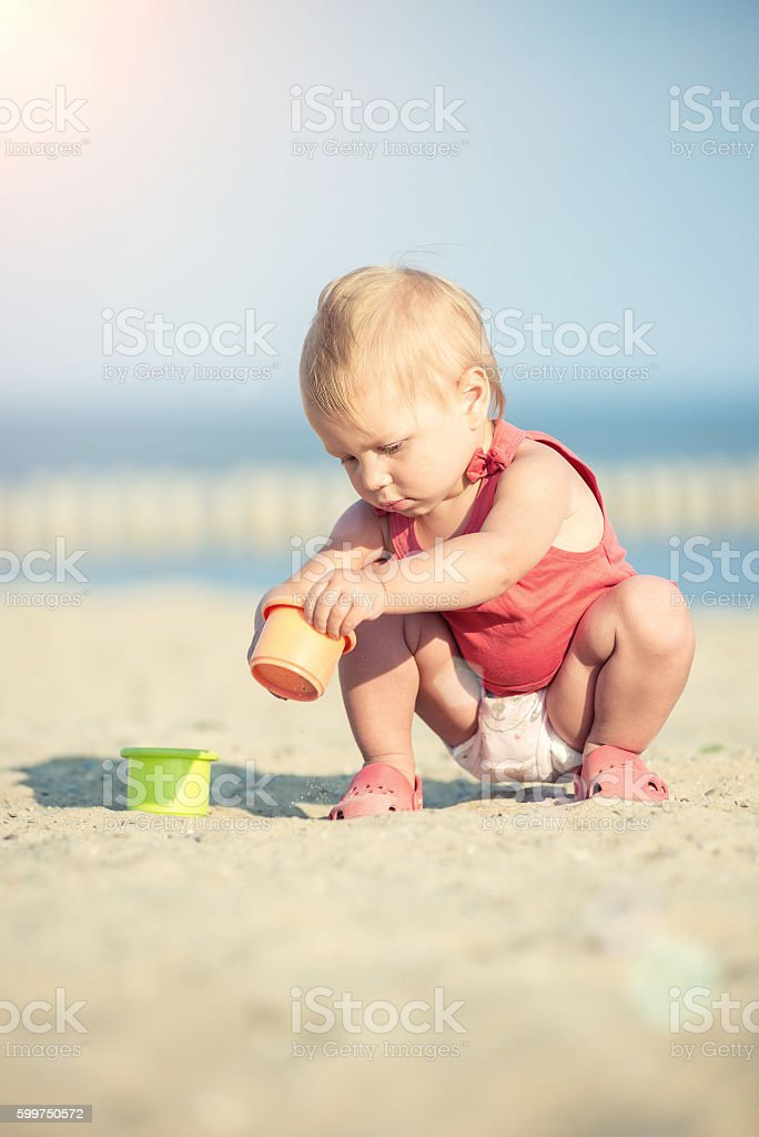 Baby girl in red dress playing on sandy beach near stock photo