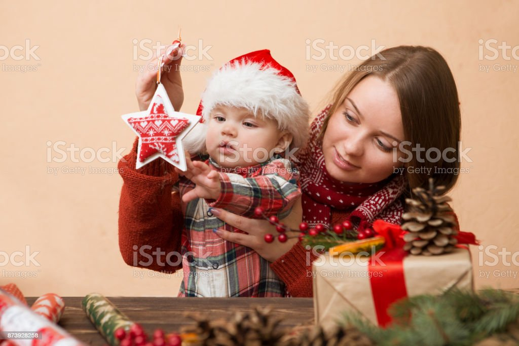 baby girl in red hat with the mother preparing gifts for christmas at home, cozy holiday interior stock photo