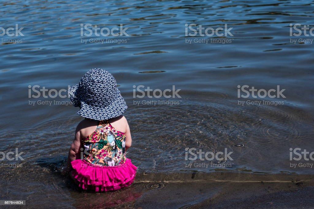 Babymädchen in Sonnenhut am See – Foto