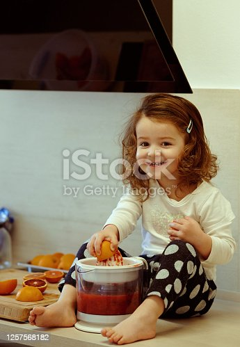 Baby girl in the kitchen juicing grapefruit looking at the camera with toothy smile