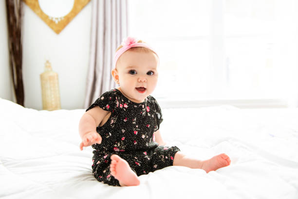 Baby girl in white bedding at home look nice A Baby girl in white bedding at home look nice 6 7 years stock pictures, royalty-free photos & images