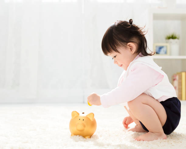 baby girl inserting a coin into piggybank stock photo