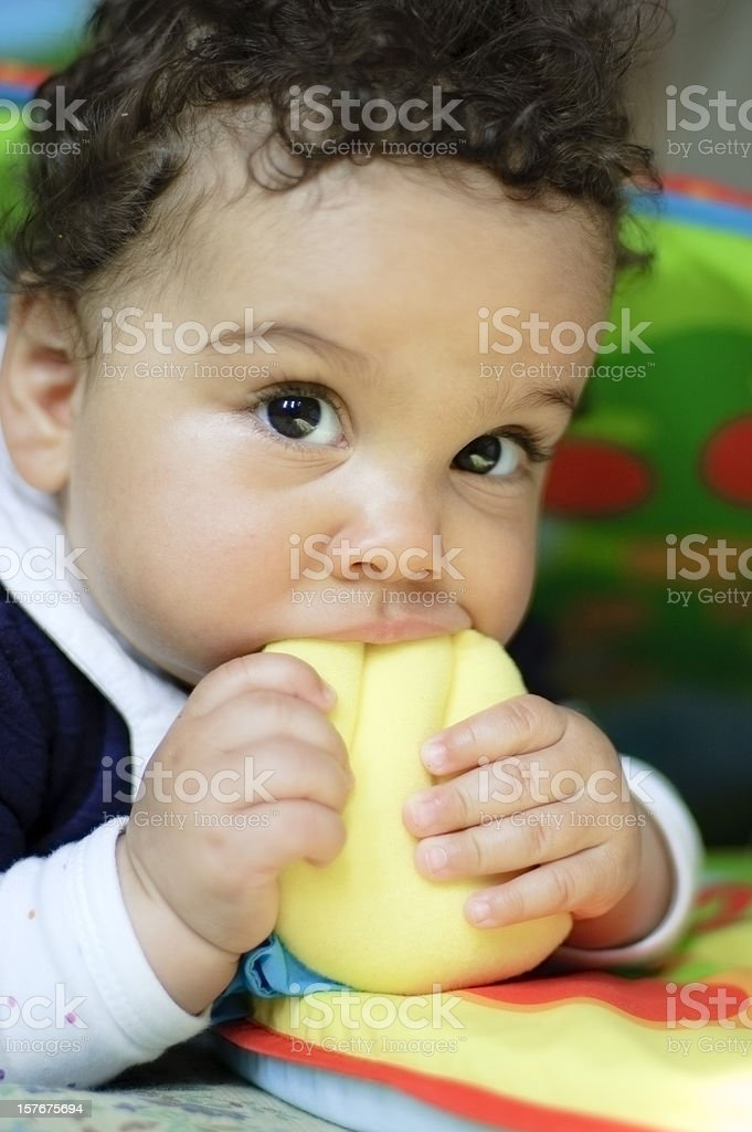 Baby Girl ( 9 months old ) is Biting Toys stock photo